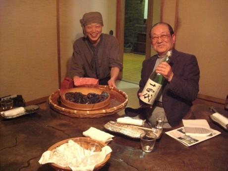 誇らしく「14代」の一升瓶をかかえているそば作り名人辻輝彦と創作料理人佐藤浩基さん